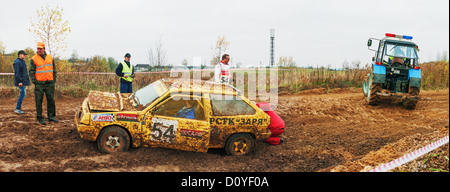 The tractor started to tow the racing car damaged on dirty road. - Stock Photo