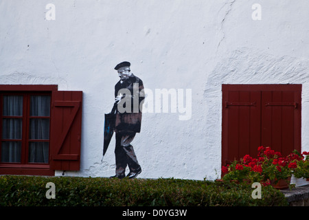 Wall Mural in the village of Burguete (Auritz) Spain of a gentleman going for a walk with his umbrella public art - Stock Photo