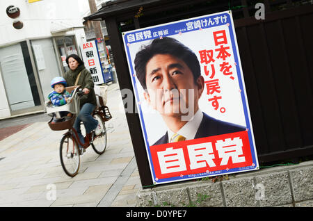 Kyoto, Japan. 4th December 2012. A woman and her child cycle past a campaign poster showing Shinzo Abe, the leader - Stock Photo