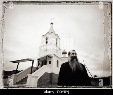 Priest standing in front of his church in Buryatia, Russia. - Stock Photo
