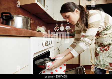 Housewife taking frying pan from oven - Stock Photo