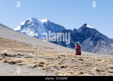 Aymara woman in the Cordillera with the mountain Huayna Potosi in background - Stock Photo