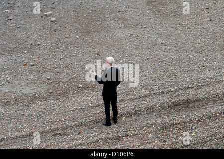 Man in suit on River Thames beach, Vauxhall, London, UK - Stock Photo
