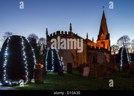 Trees covered in Christmas lights in front of St Annes church in Baslow village Derbyshire Peak District at night - Stock Photo