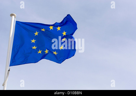 European Union flag flying in the wind in sky a slightly cloudy. - Stock Photo