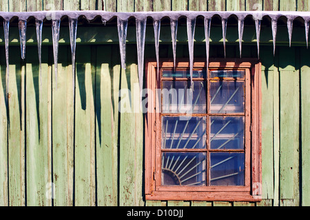 icicles which are hanging down from a roof - Stock Photo