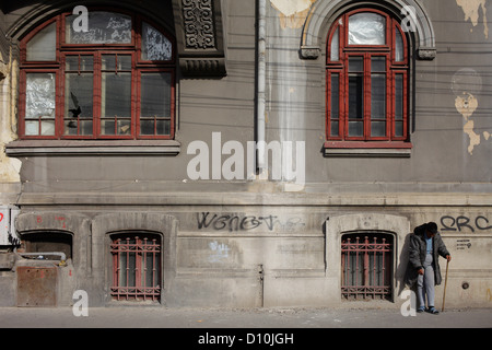 Bucharest, Romania, a man leans against an old building - Stock Photo