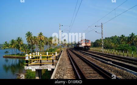 India Electric Train Running Through the Railway Bridge above Kerala Backwaters and Serene landscape of Kerala coconut - Stock Photo