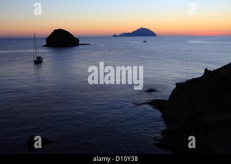 Faraglione rocks and Filicudi island seen from Pollara, Salina, Aeolian islands, Sicily, Italy - Stock Photo