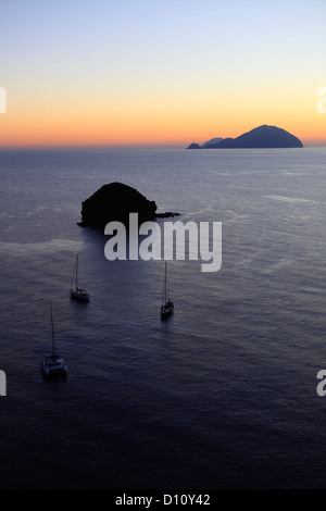 Faraglione rocks and Filicudi island seen from Pollara, Salina, Aeolian islands, Sicily, Italy - Stock Photo