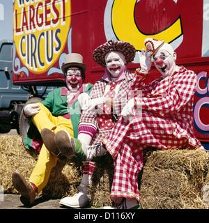1970s THREE LAUGHING CLOWNS SITTING ON HAY BALES BY CIRCUS WAGON LOOKING AT CAMERA - Stock Photo