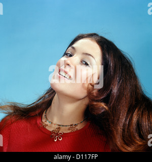 1960s 1970s PORTRAIT OF SMILING WOMAN TOSSING BACK HER LONG BROWN HAIR WEARING RED TOP LOOKING AT CAMERA - Stock Photo