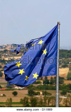 Wind torn European Union Flag on a flag pole | Vom Wind zerissene Flagge der Europaeischen Union am Flaggenmast - Stock Photo