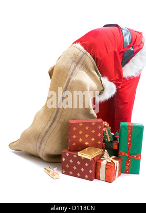 Santa Claus looking for a gift and putting his head in the gifts bag - Stock Photo