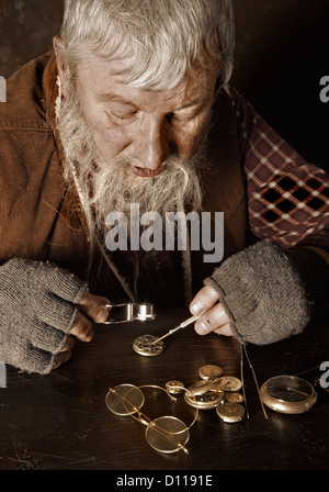 Old bearded man reparing antique watches using a magnifying glass - Stock Photo