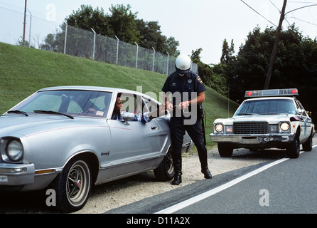 1970s POLICE OFFICER CHECKING DRIVERS LICENSE OF AFRICAN-AMERICAN DRIVER ON SIDE OF ROAD - Stock Photo