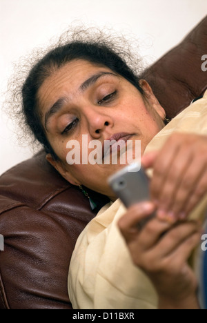 Mother who cares for daughter with Cerebral palsy taking time out to check her mobile phone for messages, London, - Stock Photo