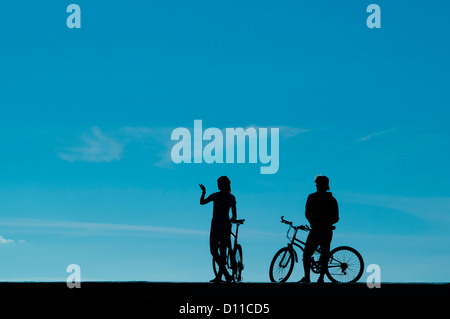 Two Cyclists man woman in silhouette on a warm October autumn afternoon, Aberystwyth Wales UK, - Stock Photo
