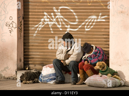 Homeless couple - man and woman  with dogs sitting beside a shop doorway in Santiago, Chile South America - Stock Photo