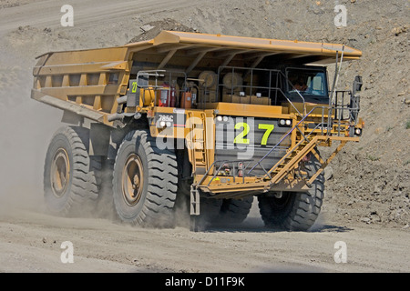 Huge mining dump truck being driven along dusty road at open cut coal mine in central Queensland Australia - Stock Photo