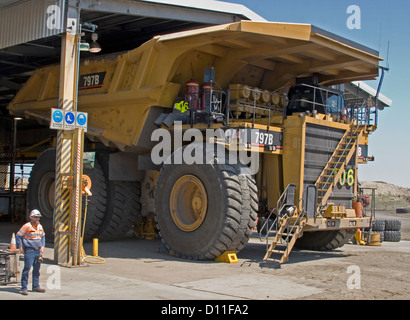 Mine worker / truck driver dwarfed by huge mining dump truck in workshop at open cut coal mine in central Queensland - Stock Photo