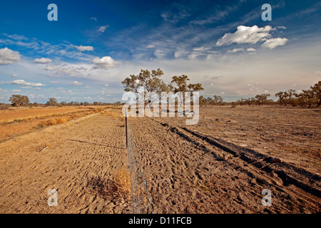 Vast arid Australian outback landscape with dusty dirt road, fence, and blue sky  in NSW, Australia - Stock Photo