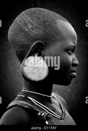 Black and white profile portrait of a mursi tribe young girl with enlarged ear with