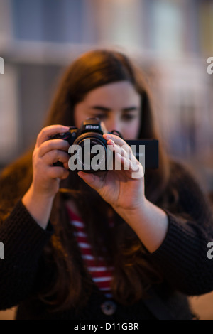 A young woman girl university media studies student making a video on a DSLR digital camera, UK - Stock Photo