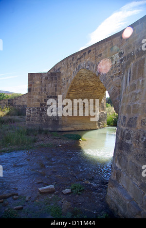 a stone bridge and sunflare, a shady spot along the French Route of the Camino de Santiago de Compostela - Stock Photo