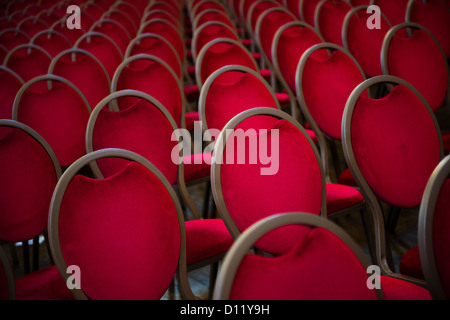 Rows of empty plush red velvet chairs in a conference hall - Stock Photo