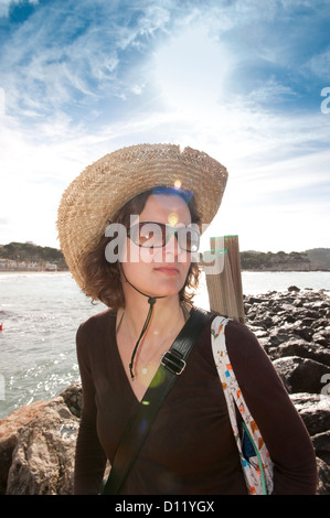 Peguera, Majorca, Spain, a woman with a straw hat and sunglasses on the beach