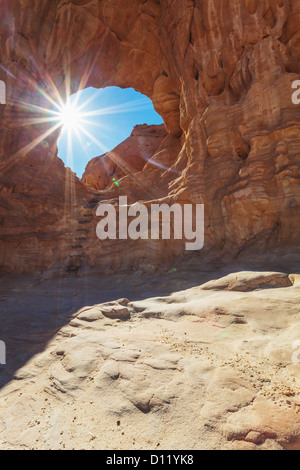 Sunlight Shining Through The Hole In A Rock Formation; Timna Park Arabah Israel - Stock Photo