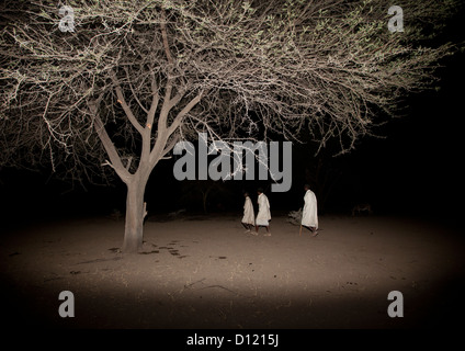 Night Shot Of Three Karrayyu Tribe Men Under A Tree During Gadaaa Ceremony, Metehara, Ethiopia - Stock Photo