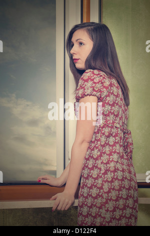 a woman in a floral dress is standing next to an open window - Stock Photo