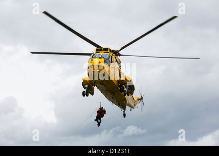Rescue Workers Hang From A Helicopter In Mid-Air; Northumberland England - Stock Photo