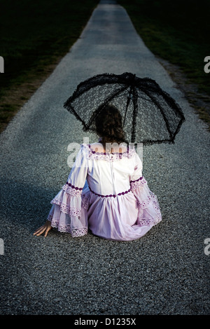a woman in a pink dress with a black lace umbrella is sitting on a street - Stock Photo