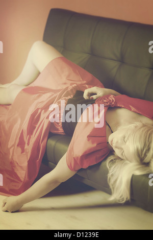 a woman in a red dress is lying on a black sofa - Stock Photo