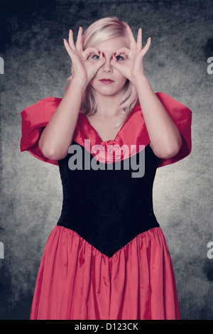 a woman in a red dress is looking trough her fingers - Stock Photo