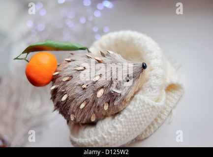 against the background of lights toy hedgehog with tangerine on a thorn - Stock Photo