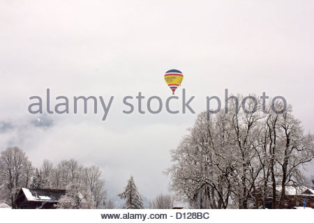 A hot air balloon in a wintery Chateau d'Oex, Switzerland - Stock Photo