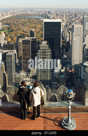 Two tourists standing on 'top of the Rock' looking north at Central park, in autumn, fall. - Stock Photo