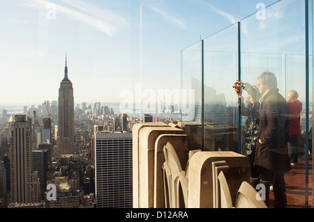 tourists standing on 'top of the rock' looking south at the Empire State Building - Stock Photo