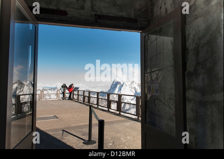 People Peering Over The Edge Of A Railing At The French Alps Mountain Range; Chamonix-Mont-Blanc Rhone-Alpes France - Stock Photo