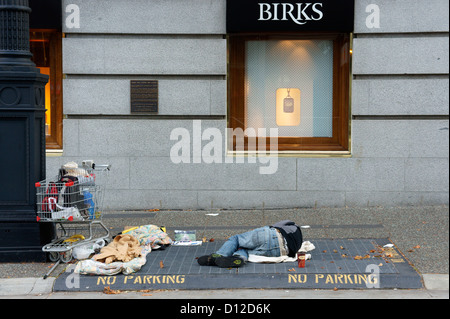 Homeless man sleeping on a sidewalk grate beside Birks jewelry store in downtown Vancouver, British Columbia, Canada