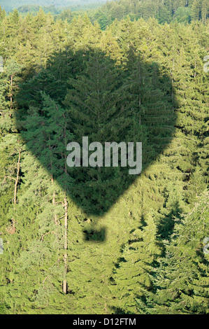 Germany, Shadow of hot air balloon over conifer forest - Stock Photo