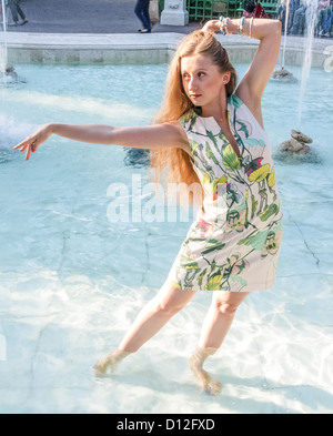 the girl dancing barefoot in the fountain - Stock Photo