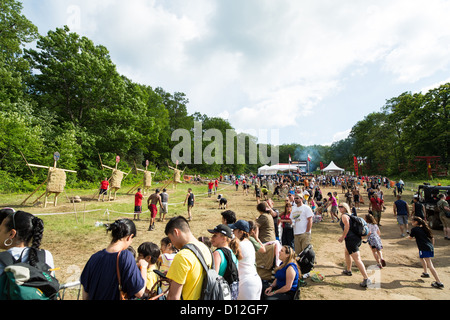 Participants of challenging sprint obstacle trail race, Spartan Race in Tuxedo New York, running in mud, jumping - Stock Photo