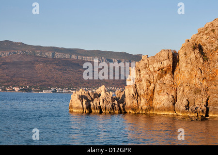 Rocky seaside and harbor in front of Crikvenica town on island Krk at sunset. Close to Silo village, Croatia. - Stock Photo