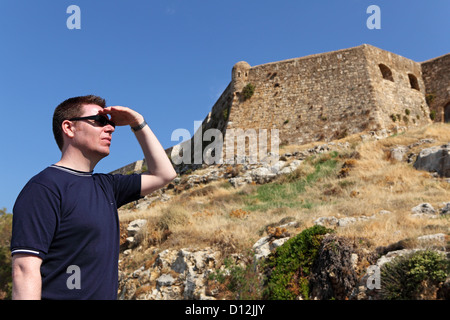 A tourist looks towards the walls of the Fortezza (the fortress) in the old town in Rethymnon, Crete, Greece. - Stock Photo