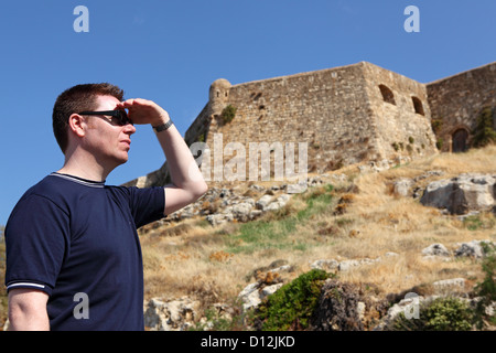 A tourist looks towards the walls of the Fortezza (the fortress) in the old town in Rethymno, Crete, Greece. - Stock Photo